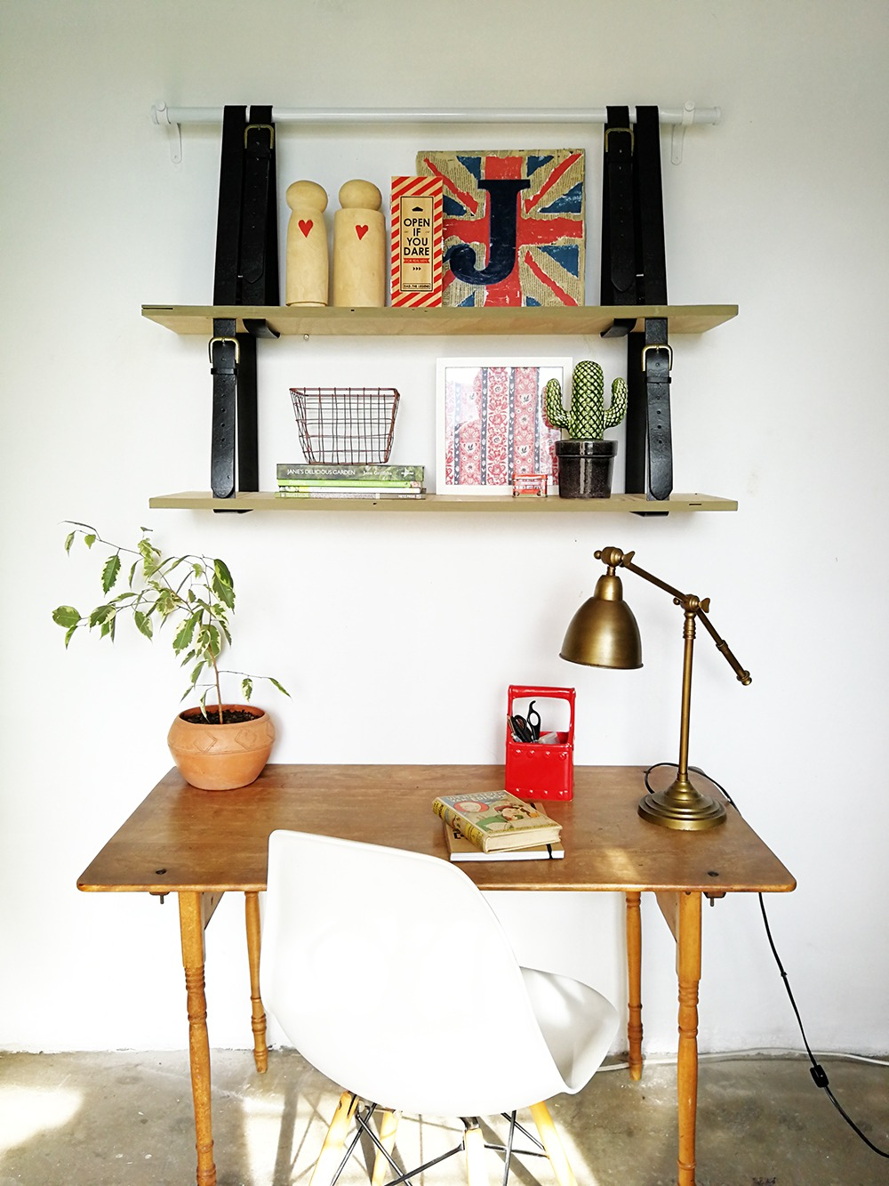 hanging-belt-shelf-in-a-home-office-with-a-wooden-desk-and-copper-table-lamp-and-red-details